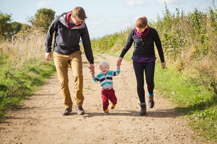 Parents and a child walking along a footpath in the countryside.の写真素材 [FYI02256715]