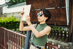 A woman using a tablet to take a photograph at a historic temple.の写真素材 [FYI02256729]