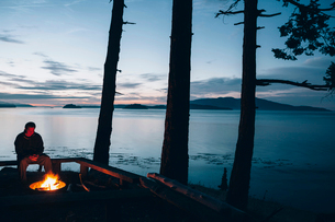 Man sitting by campfire at dusk, San Juan Islands in the distance, Washington, USA.の写真素材 [FYI02256737]