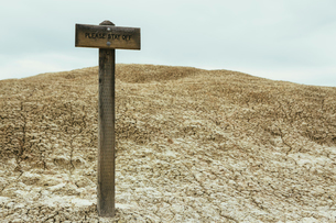 Cracked parched soil surface of the desert, and a Please Stay Off sign on the surface of the desertの写真素材 [FYI02256761]