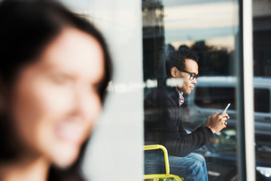 A seated man seen through a window looking at a cellphone, with an out-of-focus woman in the foregroの写真素材 [FYI02256773]