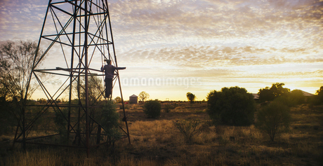 A person climbing a pylon in a rural landscape.の写真素材 [FYI02256779]