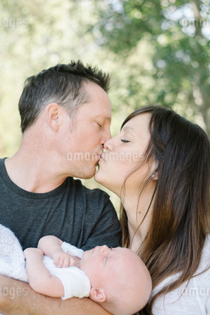 Parents holding a small baby and kissing, a group portrait.の写真素材 [FYI02256783]