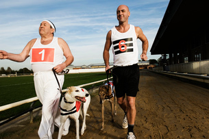 Two men in sportswear running on a racetrack with two greyhounds on leads.の写真素材 [FYI02256795]