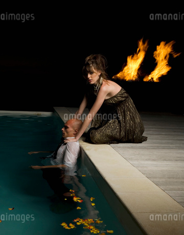 Woman kneeling on the edge of a swimming pool, touching shoulders of man inside pool, flames in theの写真素材 [FYI02256870]