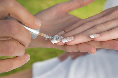 Close up of woman having her fingernails painted.の写真素材 [FYI02256893]