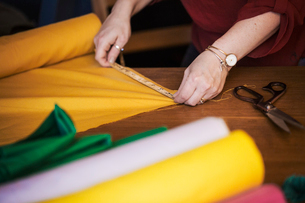A woman using a tape measure to measure yellow fabric for cutting out.の写真素材 [FYI02256911]