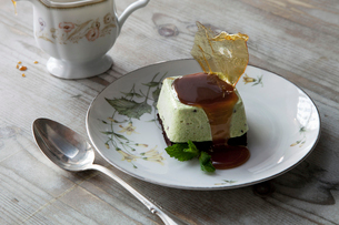 A sweet dessert dish with sugarwork and sauce on a china plate, with spoon and cup.の写真素材 [FYI02256932]