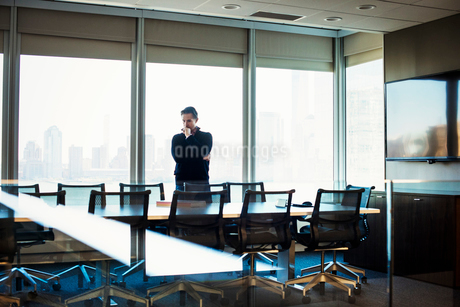 A man standing at a table in a meeting room looking down at an open book.の写真素材 [FYI02256939]