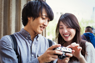 Young Japanese man and woman enjoying a day out in London, holding at a digital camera, smiling.の写真素材 [FYI02256945]