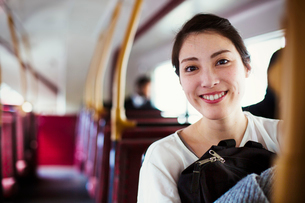 Young Japanese woman enjoying a day out in London, riding on a double decker bus.の写真素材 [FYI02256949]