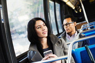 A young man and a young woman sitting on public transport holding their cellphones and looking arounの写真素材 [FYI02256966]