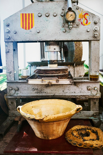 An olive press, a mechanical crusher with press and a small stream of olive oil flowing into a bowl.の写真素材 [FYI02256977]