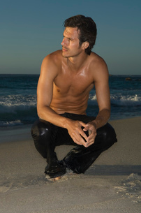 Shirtless man in wet jeans squatting on a sandy beach.の写真素材 [FYI02256995]