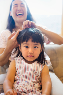 Family home. A mother combing her daughter's hair.の写真素材 [FYI02257009]