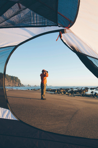 Man framed by camping tent, standing on beach and looking through binoculars at dusk, Olympic Nationの写真素材 [FYI02257035]