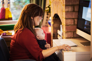 A woman seated with a baby on her lap using her computer, both watching the screen.の写真素材 [FYI02257055]