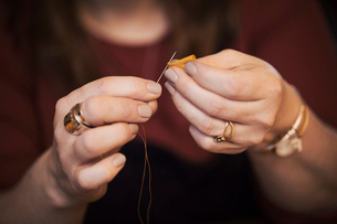 A woman using a needle threaded with cotton thread.の写真素材 [FYI02257058]