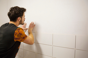 A builder, tiler placing white ceramic tiles on a wall in a bathroom.の写真素材 [FYI02257068]