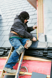 A man at the top of a ladder on a house roof, fixing tiles on a dormer roof.の写真素材 [FYI02257076]