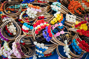 A market stall selling woven hairbands with small fabric flowers.の写真素材 [FYI02257088]