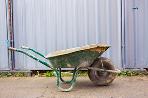 Green wheelbarrow on a building site in front of a metal container.の写真素材 [FYI02257100]