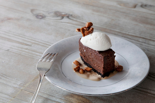 A slice of  chocolate mousse dessert with ice cream, nuts and sauce on a plate.の写真素材 [FYI02257107]