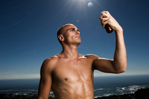 Shirtless man standing in front of ocean, holding aloft bottle of suntan lotion.の写真素材 [FYI02257118]