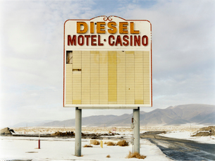 A large roadside sign in a flat landscape with light snow. Mountain range. Diesel and Motel Casino.の写真素材 [FYI02257135]