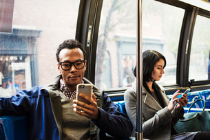 A young man and a young woman sitting on public transport looking at their cellphones.の写真素材 [FYI02257163]