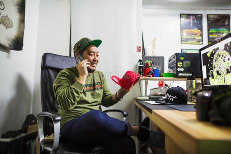 Design Studio. A man sitting at a desk making a phone call.の写真素材 [FYI02257194]