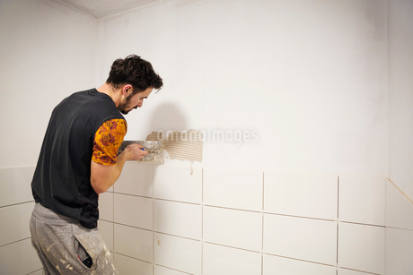 A builder, tiler placing white ceramic tiles on a wall in a bathroom.の写真素材 [FYI02257199]