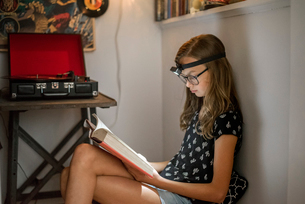 A girl reading a book in a quiet corner using a head torch.の写真素材 [FYI02257222]