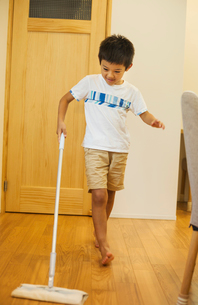 Family home. A boy with a mop cleaning a wooden floor.の写真素材 [FYI02257230]