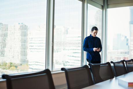 A man standing next to a table in a meeting room looking at a cellphone.の写真素材 [FYI02257272]