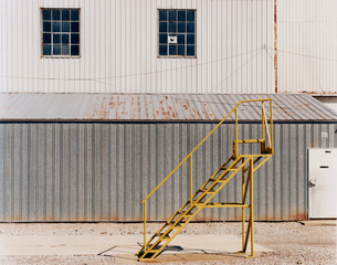 A ladder beside an industrial unit, with corrugated iron walls.の写真素材 [FYI02257286]