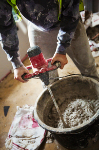 A builder mixing plaster using an electric mixer in a bucket on a construction site.の写真素材 [FYI02257291]