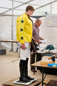 Jockey in a yellow shirt standing on weighing scale, being weighed before a horse race.の写真素材 [FYI02257293]