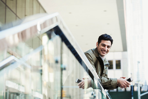 A young man leaning over a balcony rail holding a cellphone and smiling.の写真素材 [FYI02257301]