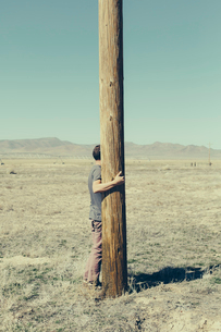 Man with his arms around a wooden utilities pole, clinging to or hugging the post in a flat open lanの写真素材 [FYI02257304]