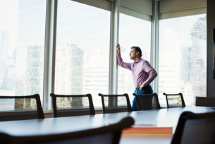 A man in a meeting room looking out of a window at an urban landscape.の写真素材 [FYI02257308]
