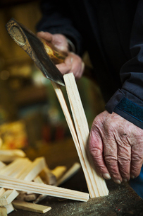 Close up of a man in a sailmaker's workshop splicing wooden pegs with a hand axe.の写真素材 [FYI02257309]