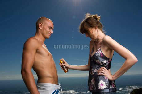 Shirtless man and woman standing in front of ocean, woman applying suntan lotion to man's stomach.の写真素材 [FYI02257315]