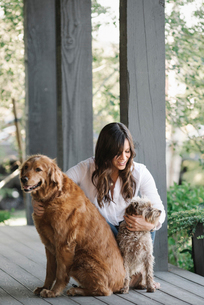 A woman on a porch patting her two dogs.の写真素材 [FYI02257338]