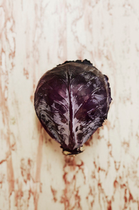 A shot of a head of red cabbage on a wooden surface, seen from above.の写真素材 [FYI02257339]
