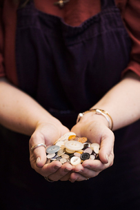 A woman holding hands full of buttons, varied shapes and sizes.の写真素材 [FYI02257340]
