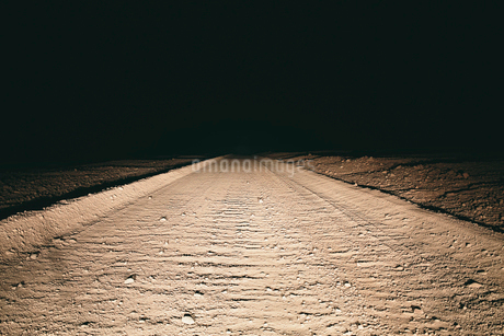 Dirt road in desert illuminated by car headlights, Death Valley National Park, USAの写真素材 [FYI02257348]