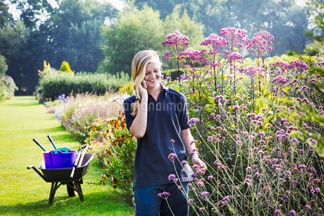 Female gardener at Waterperry Gardens in Oxfordshire, using a mobile phone.の写真素材 [FYI02257354]