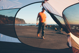 Man walking on beach at dusk, camping tent in foreground, Olympic National Park, Washington, USA.の写真素材 [FYI02257383]