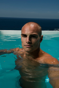 Bald young man in a swimming pool.の写真素材 [FYI02257407]